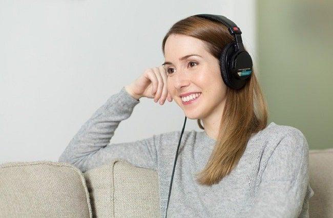 زنی در حال گوش دادن به موزیک با هدفون